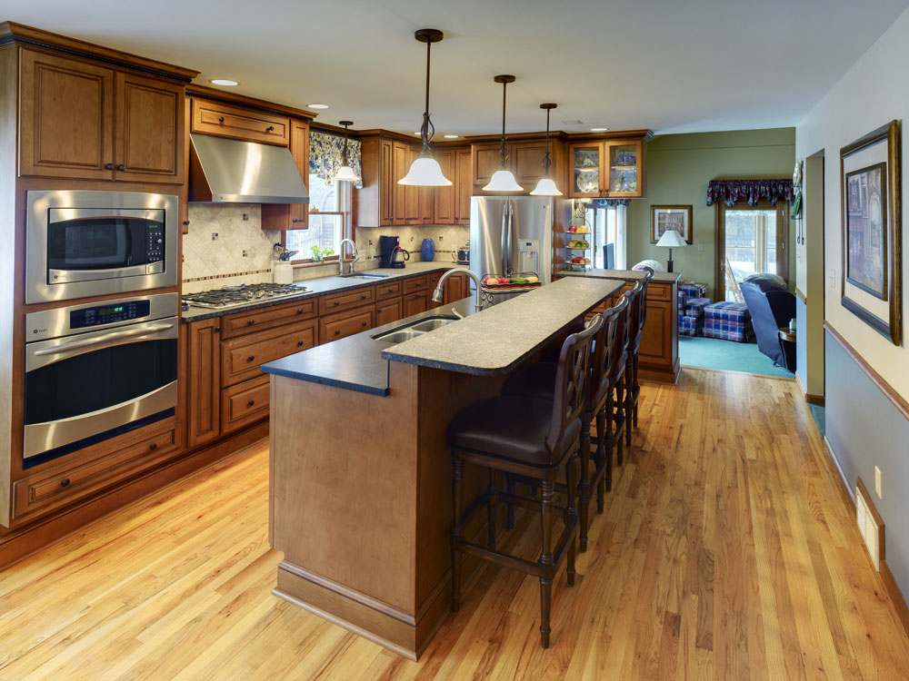 The stylish cabinetry in this kitchen has a chocolate glaze finish with distressed drawers and doors. A two-tiered island provides an area for food prep and seating for four. Other features in the kitchen include two sinks (one in the island), a wall cabinet with glass doors that displays china over a peninsula open to a family room. The peninsula can serve as a buffet area when entertaining guests.