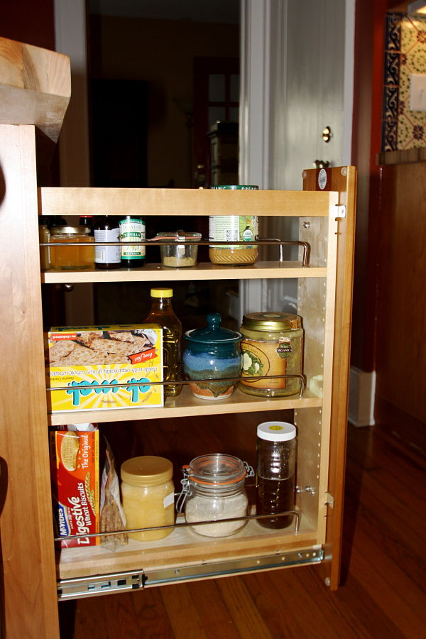 "The owners enjoy cooking so functional storage was a ""must have."" Pullout and open storage keep supplies and cookbooks at hand."