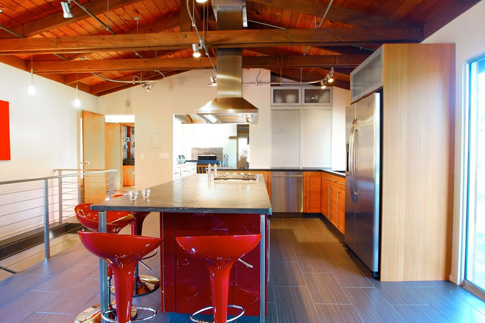This award-winning kitchen features a bright red island with jet black granite surface. Cabinetry includes an aluminum tambour garage with exotic wood grain perimeter cabinets. The cable railing system, aluminum exhaust hood and unique cabinetry give this kitchen an updated, contemporary feel.