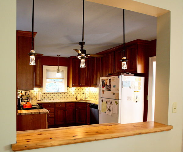 "The original natural cherry cabinets were maintained. New cabinets were matched to blend with the old. The new semi-custom cabinets used were from Jim Bishop Cabinets, in the ""Jamestown"" door style with a ""Natural High Sheen"" finish. The owners updated the countertops, sink and backsplash in the original u-shaped footprint of the kitchen. They retained the appliances. Cabinet hardware was replaced."