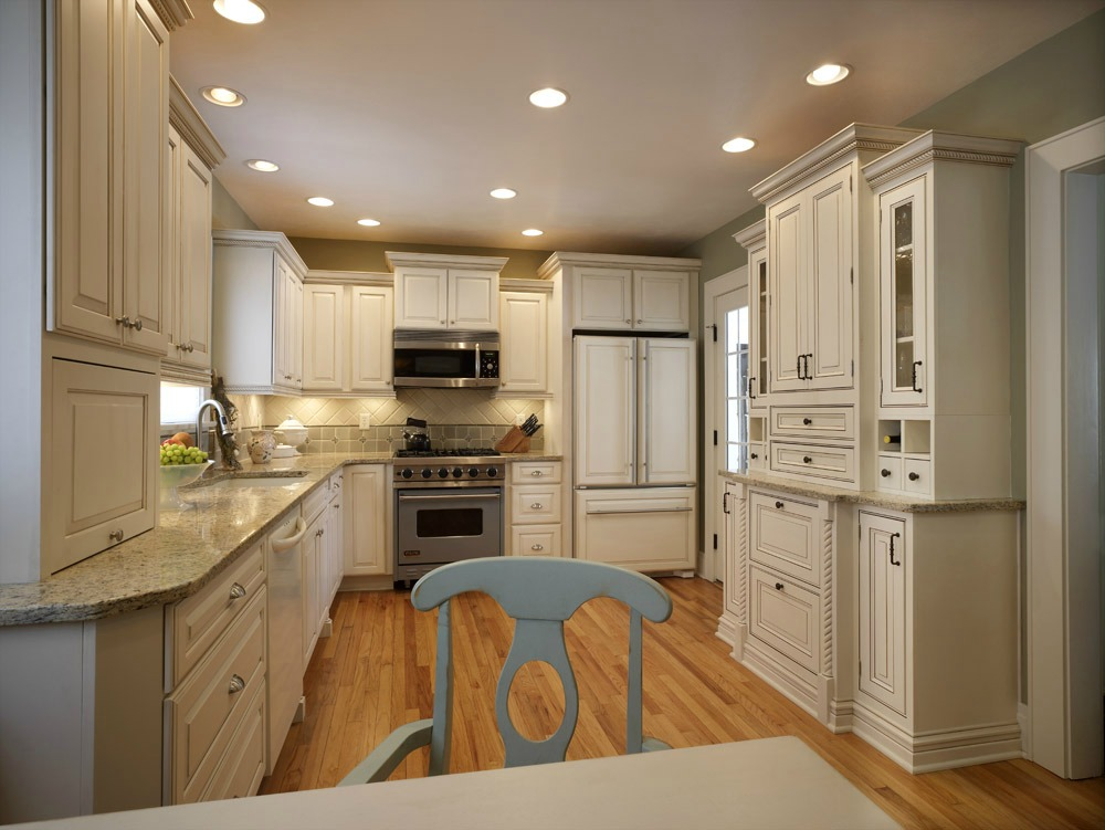 The kitchen is the center of activity in many homes. The large wall of cabinets serves as a command center concealing a telephone and compartments for family mail, calendars and cookbooks. Painted cabinets and granite countertops make this space a bright gathering place for family fun and entertaining.