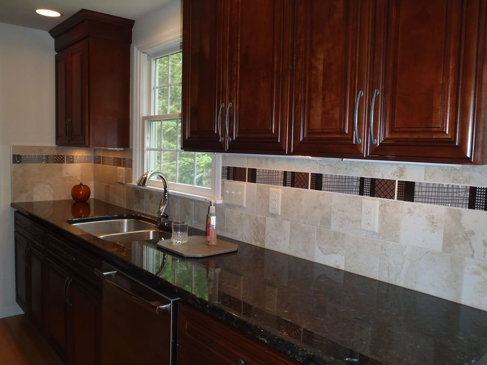 "Recessed and under-cabinet lights provide task lighting on the counter areas. Backsplash field tiles are from Best tile. They are 6-by-6 inch Roman Travertine tiles in Silver and the accent tile is Dobkin Brown ""Matrix Listello"". The backsplash adds both function and style to the kitchen."