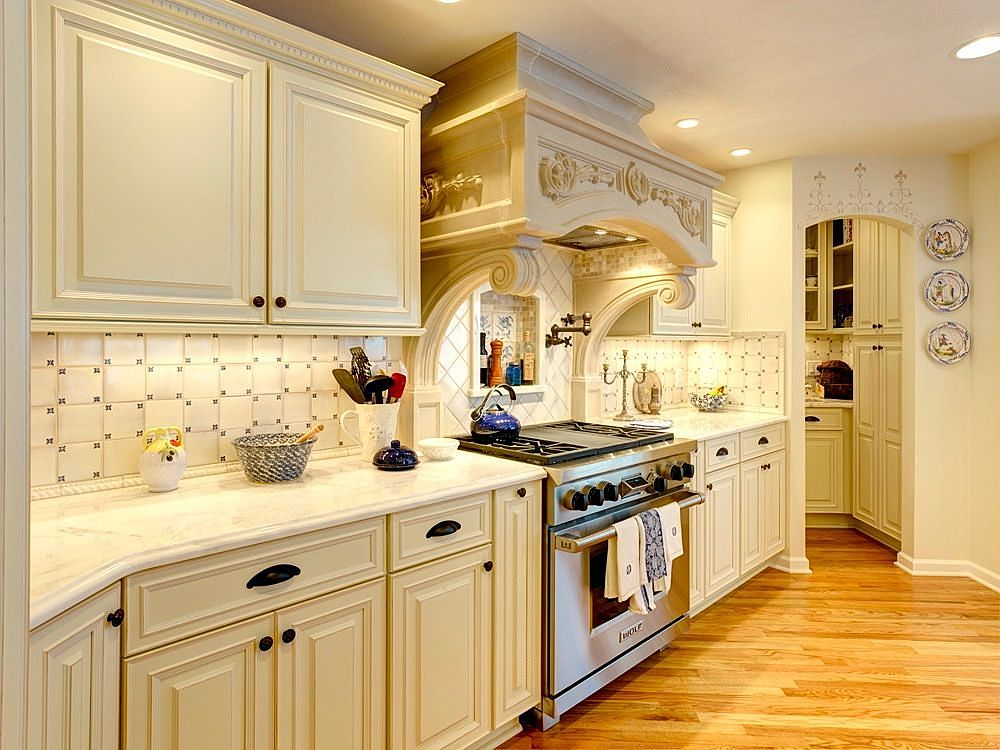 "The kitchen features a 1000 lb. ""Old Stone Works"" range hood that matches the fireplace mantel. The kitchen cabinets are from the ""Bishop Cabinets"" line of custom cabinets and feature an off-white painted finish with edge wear and oil rubbed bronze hardware. The perimeter counters are marble."