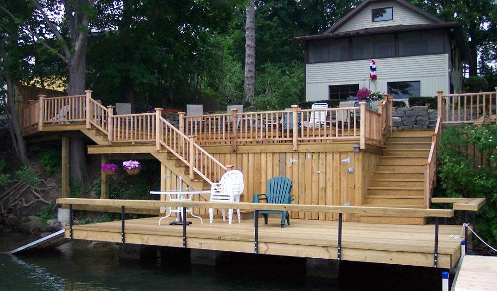 Dock Design Ideas boat dock transformed into lounge features vaulted paneled ceiling dotted with ceiling fans over white slipcovered sofa and white slipcovered chair accented This Deck Over The Water Includes Concealed Storage Areas A Ramp Into The Water And
