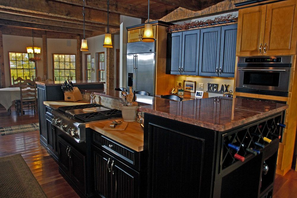 This elegant rustic kitchen combines distressed painted cabinetry with natural finished cabinets. A multi-level, multipurpose island provides space for food prep, cooking and entertaining. Granite and butcher-block countertops provide style and functionality.
