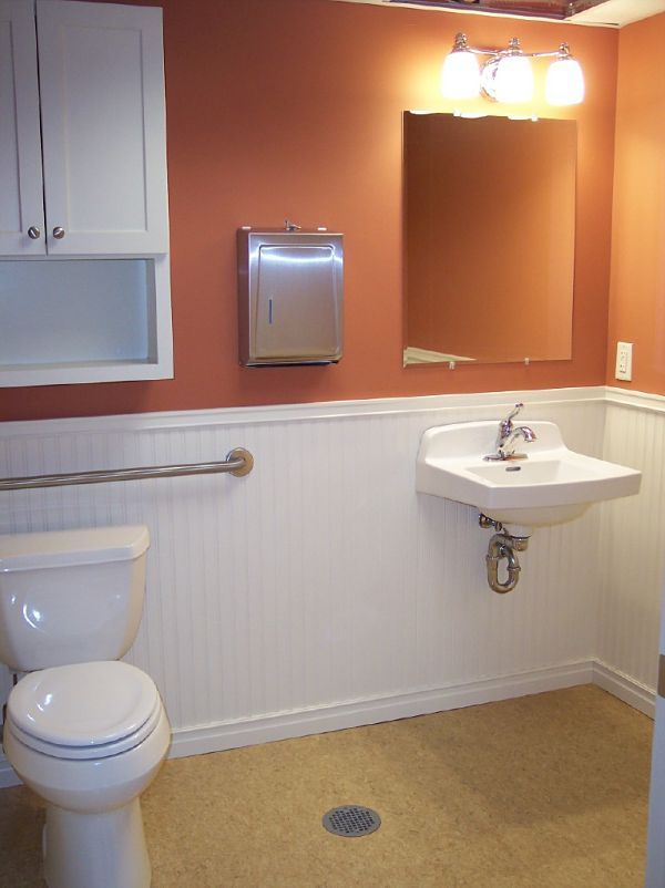 Commercial bathrooms must be designed to be handicap accessible. An example of this, this bathroom includes grab bars and a wall mount sink for easy access. The floor space of the bathroom is large allowing maneuverability of a wheelchair.