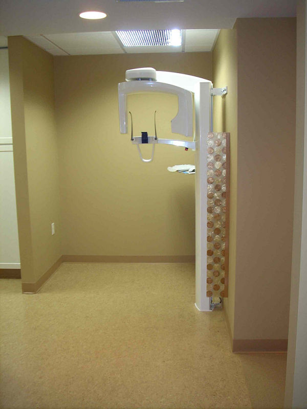 Medical offices have unique code requirements. Equipment, such as this x-ray machine, requires special wiring and wall structure to protect both the unit and the people using it. For aesthetics, this x-ray room includes a custom translucent panel beside the x-ray machine, and a wall concealing the mechanicals from plain view.