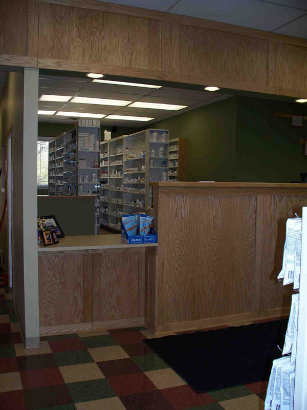 The desktop shown at this pharmacy includes a large overhang so a person in a wheelchair can wheel in underneath and use the surface comfortably. The low height of the desktop makes it usable by people of all different heights.