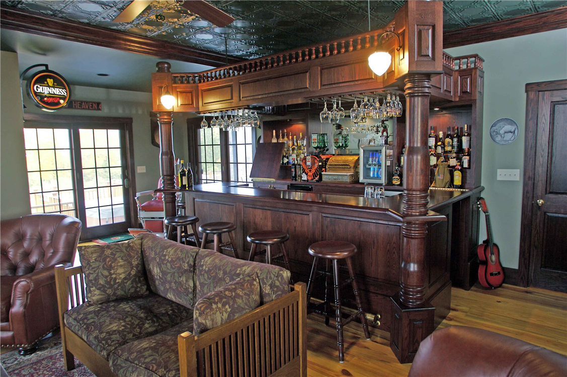 This bar was designed to meet the guidelines given to us by the owner. Some of the bars features include a sink, built in electric, a brass foot-rail, four large hand-turned columns and over 200 hand turned spindles on the top rail. The bar room also includes a tin ceiling with its own bathroom and pool room off to the sides.