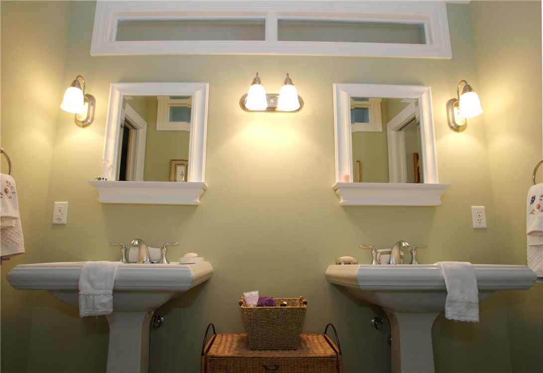 Twin pedestal sinks with matching bathroom hardware create a mirror image of each other in this Jack and Jill style bathroom linking two bedrooms.