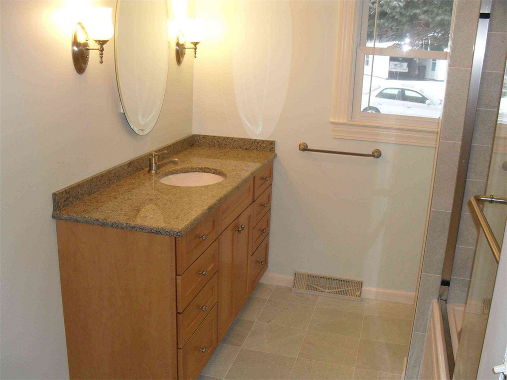 A sleek shower unit marble counter top and stained cherry cabinetry make this small bath appear for Bathroom remodeling syracuse ny
