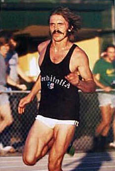 Short Shorts Vintage Tank Top With USA Or Adidas Similar Logo Mustache Shaggy Hair That Is A Costume In And Of Itself