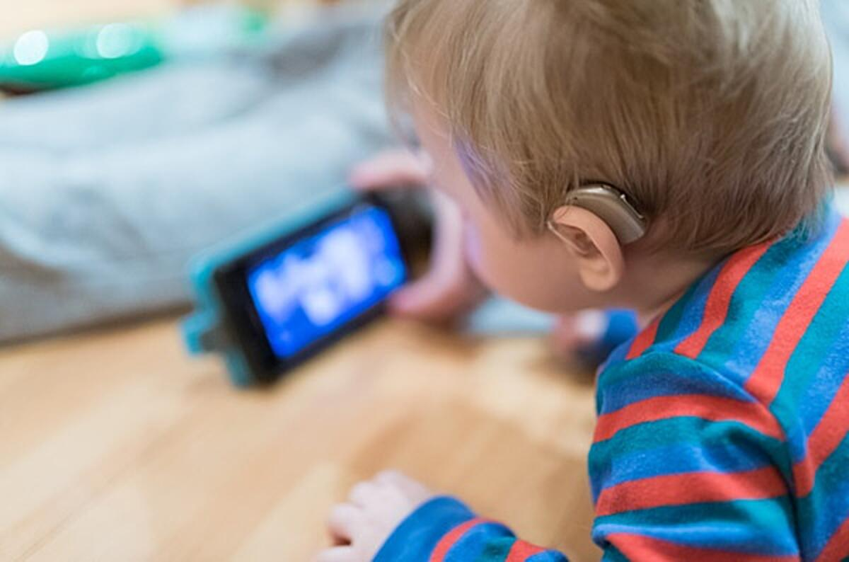 Click the photo of a baby with a hearing aid watching a video on a phone to find out how we all win with accessibility.