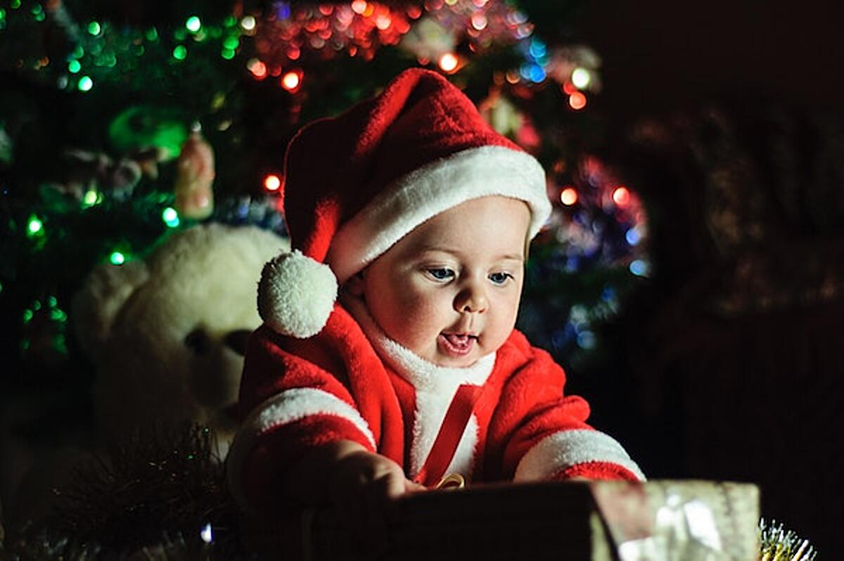 A baby in a Santa suit opens a present. Click the photo read about Christmas giving: what charities really want you to donate on the The Spinoff.
