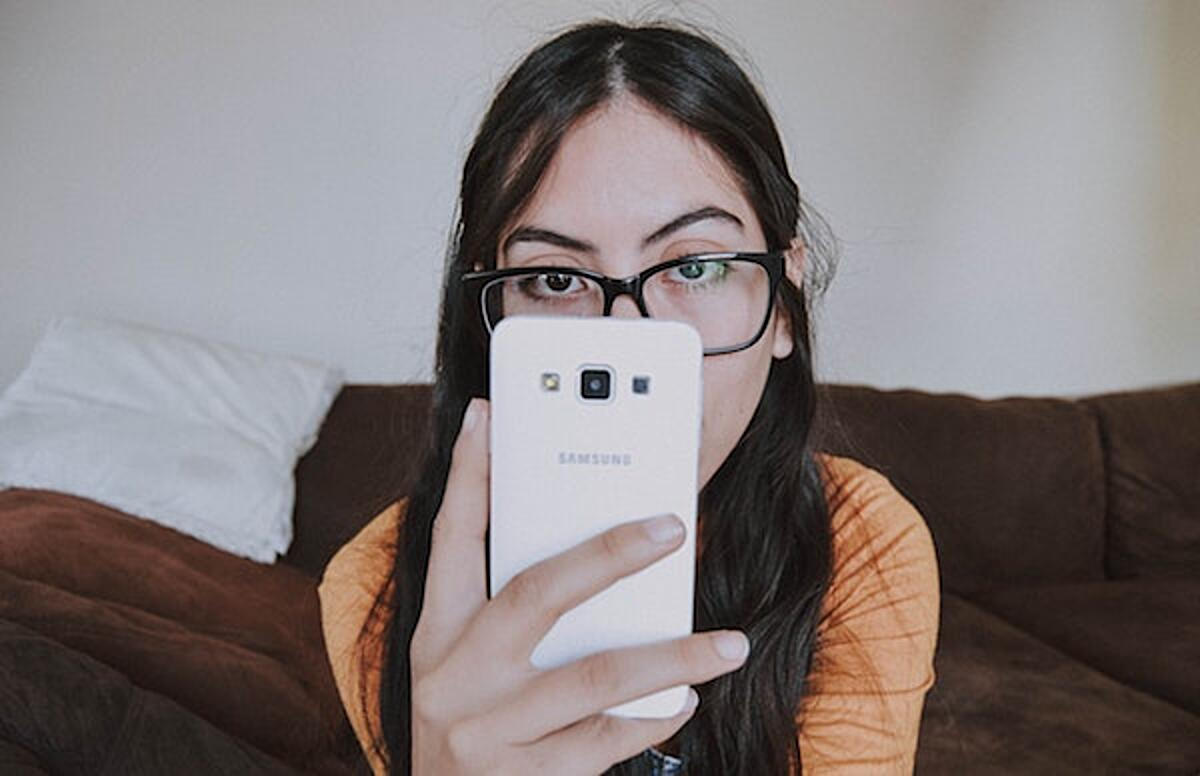 Click the photo of a woman wearing glasses using a smartphone to give feedback on the new standards. Photo by Bianca Castillo on Unsplash.