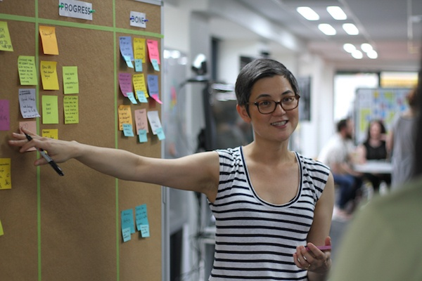Click the photo of a Product Owner in front of a Scrum board to view the post on how Agile transparency reduces project risk.