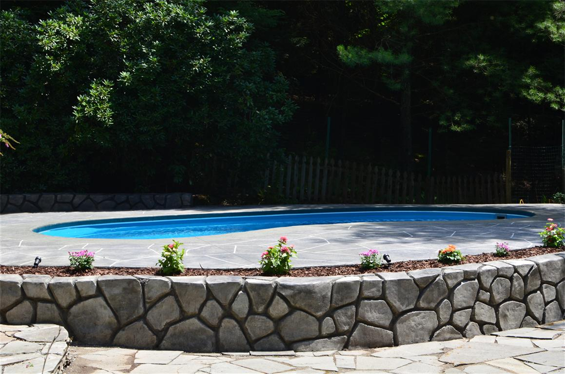 StoneMakers Retaining wall & Leisure Pools Tuscany 29 Fiberglass swimming pool in Queensland Blue. Location: Sullivan County, NY