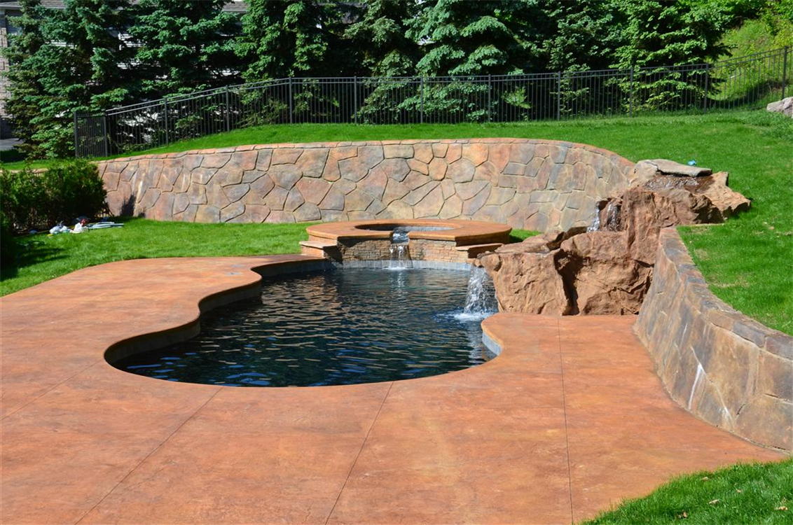 StoneMakers Retaining Wall, Waterfall, and Patio with Leisure Pools Grand Riviera 40 Fiberglass Swimming Pool and matching Sorrento spillover spa in Outback Blue. Location: Central Valley, NY