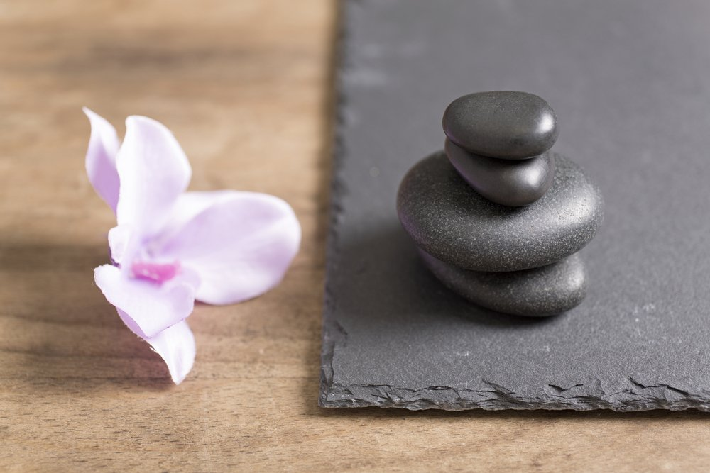 Pile of four spa stones with a fresh orchid flower next to it on a slate tray