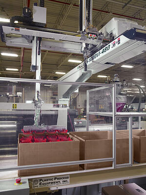 red plastic injection molded parts being stacked into a box in Rodon's facility by an automated arm