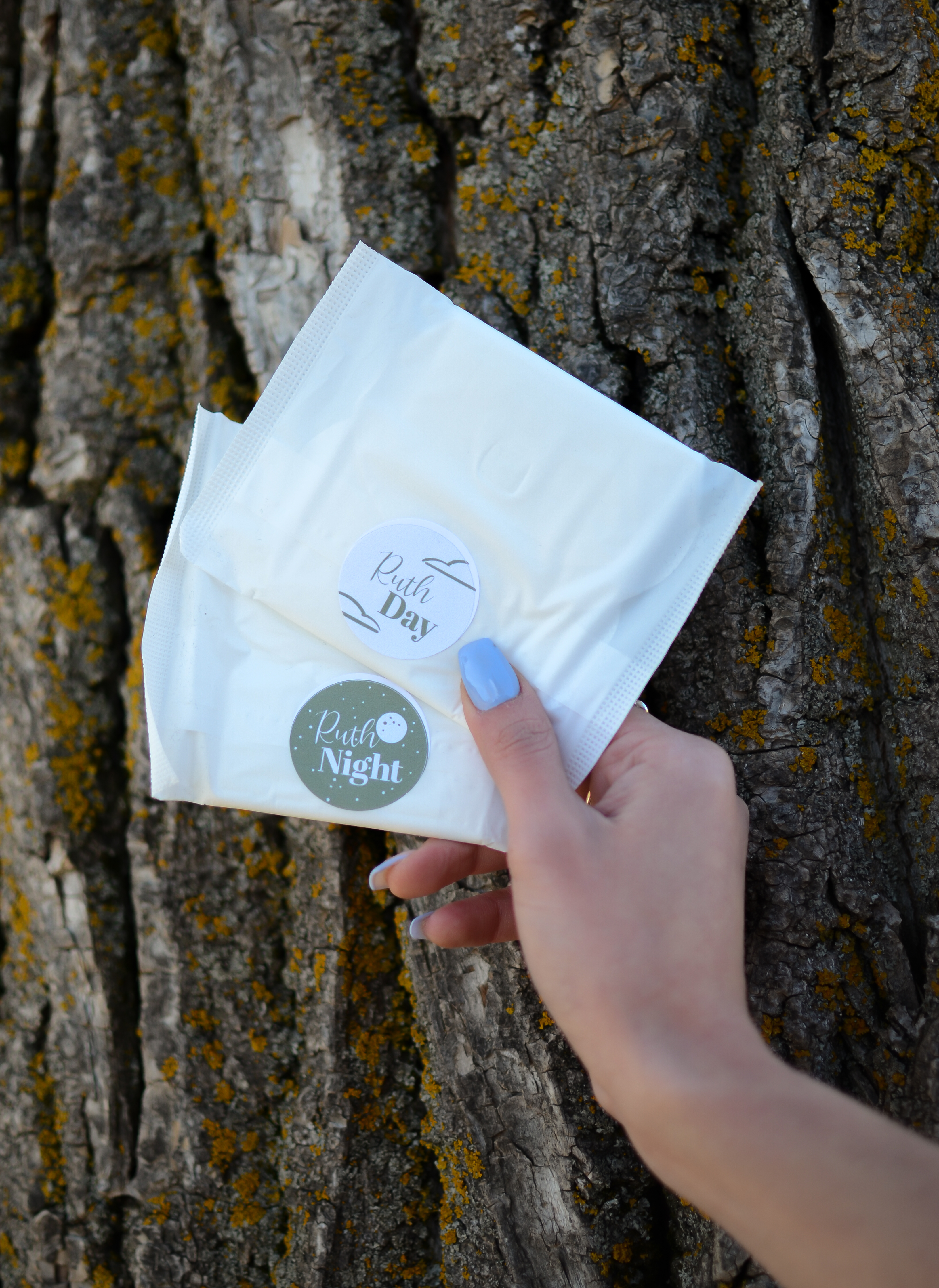 Hand holding Ruth Day Pad and Night Pads against tree trunk