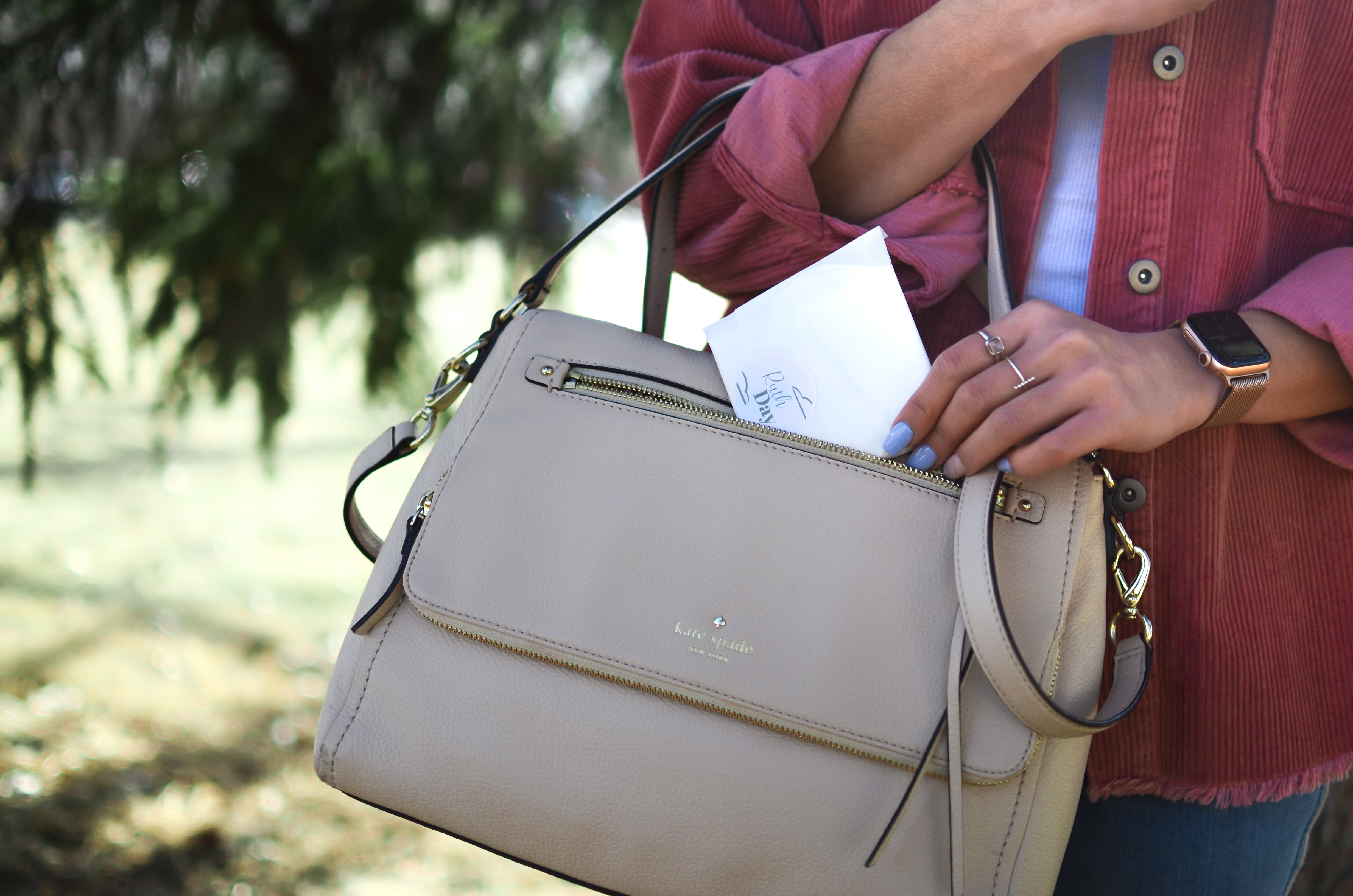 Ruth Day pad being taken out of beige handbag