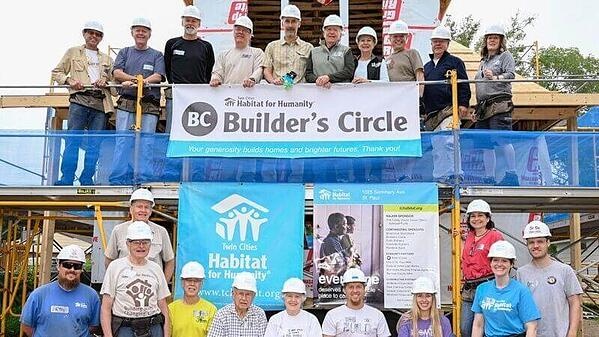 A group from the Builder's Circle Build standing around the Builder's Circle and TC Habitat signs.