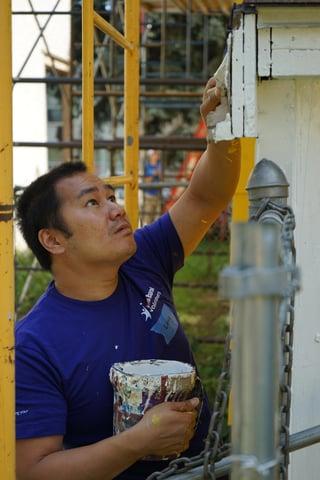 A U.S. Bank volunteer focuses on painting Cassandra's home.