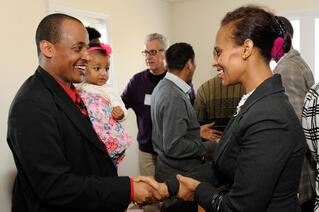 Samson, one of the two homebuyers being recognized at the dedication, is congratulated.