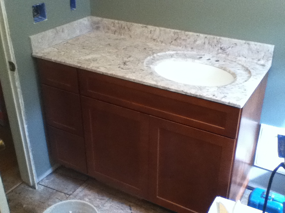 bathroom vanity installation with marble counter top and back splash