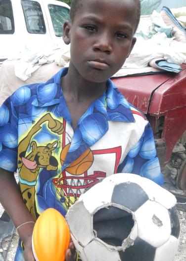 This child's soccer ball was broken, but the volunteers at Schools for Haiti changed that.