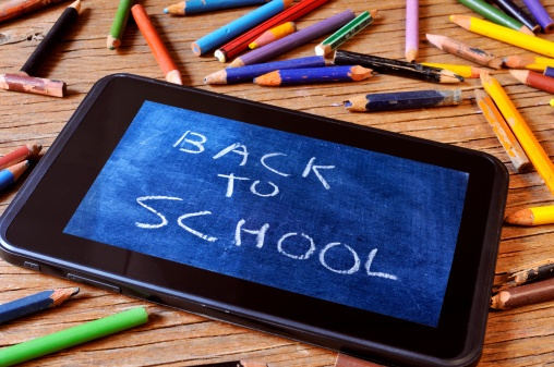 "tablet surrounded by broken pencils with ""back to school"" written on it like a chalkboard"