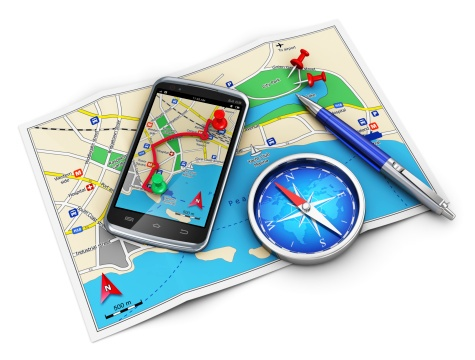 a smartphone with a maps app overlaid on top of a map with a compass and pen