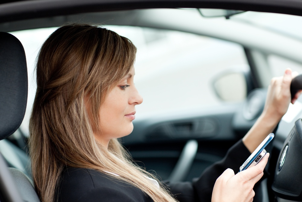 Beautiful businesswoman sending a text while driving to work.jpeg