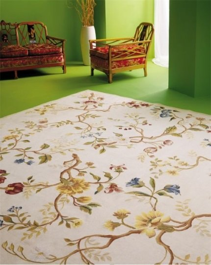 A cream, blue, red, yellow and green floral needlepoint rug in green living room with Chinoiserie and contemporary furniture