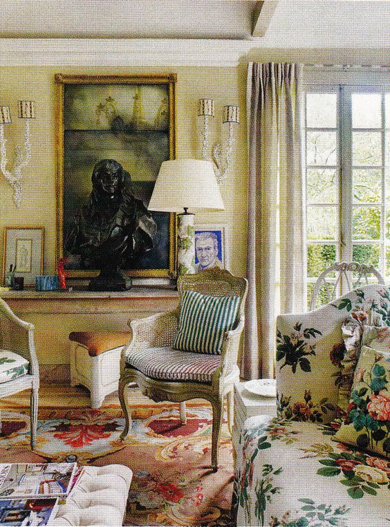 A beige and red Aubusson rug provides a dramatic contrast to the floral chintz fabrics as in the English hunting lodge of designer Nicky Haslam.