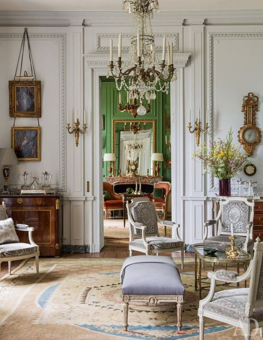A beige and blue Neoclassical Aubusson rug paired with white walls and pale upholstery can create a modern atmosphere in a traditional French room as in the living room.