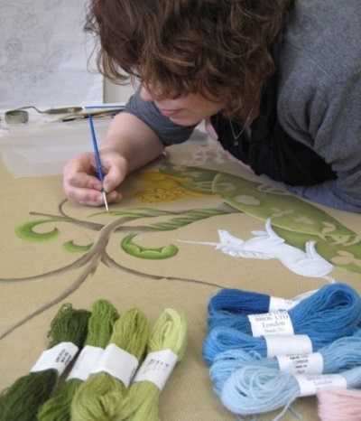 Artist painting a needlepoint rug pattern on a canvas