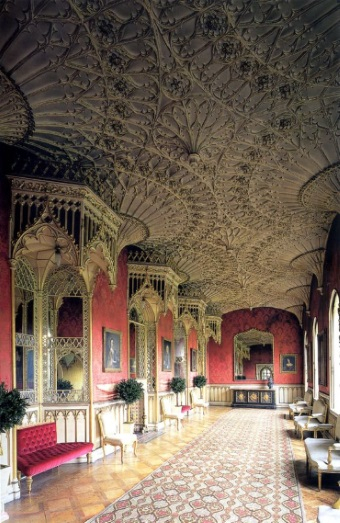 Elizabethan needlepoint rug in cream, red, gold and charcoal complements ornate ceiling and red walls in the Grand Gallery, Strawberry Hill House, Twickenham, London