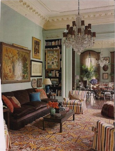 An antique red and gold damask needlepoint rugs complements green walls, brown silk sofa and and red, gold and blue striped upholstered chairs in a handsome English living room