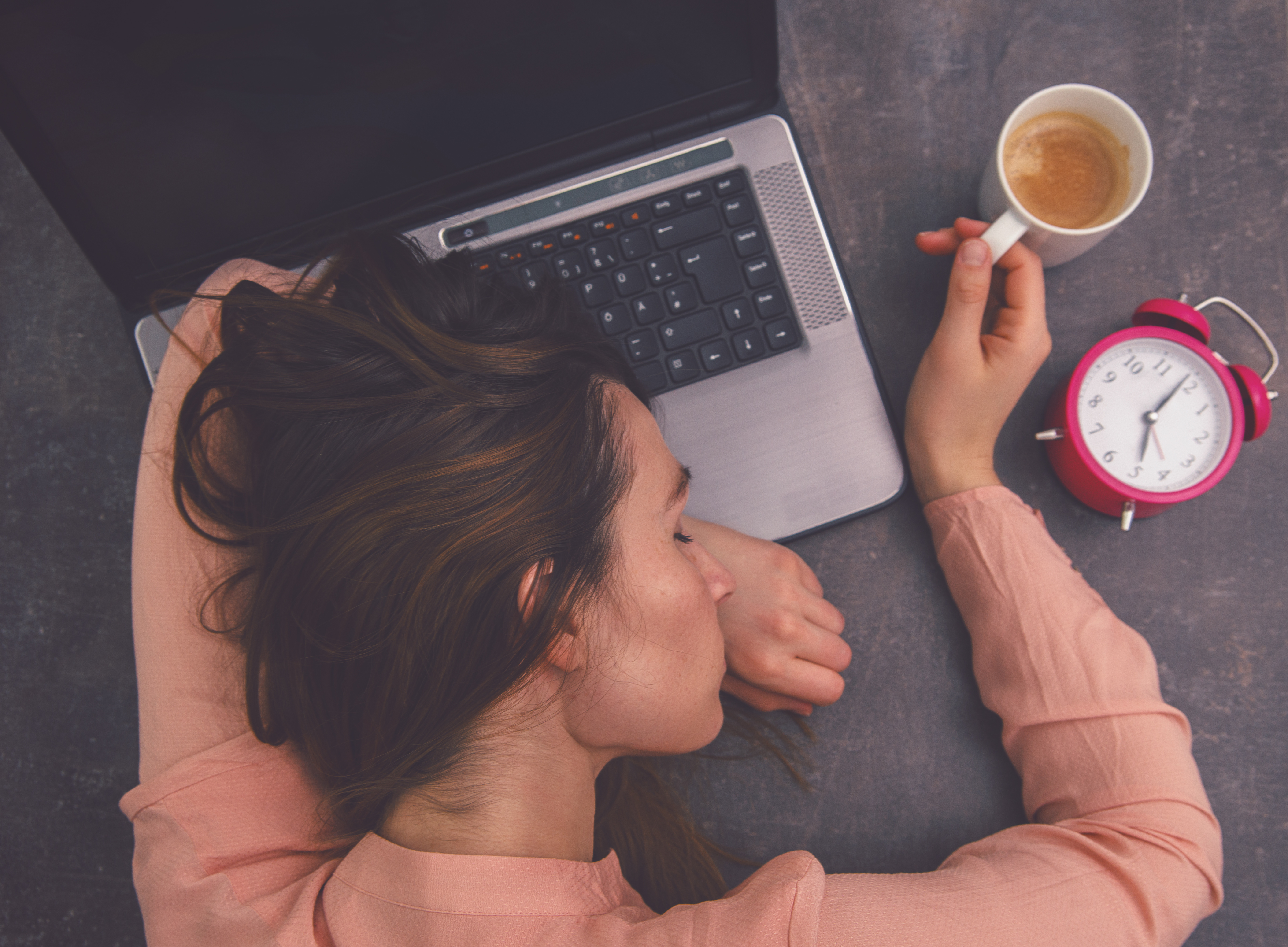 A woman lays her head on her laptop while loosely grasping the handle of a coffee mug on her desk.