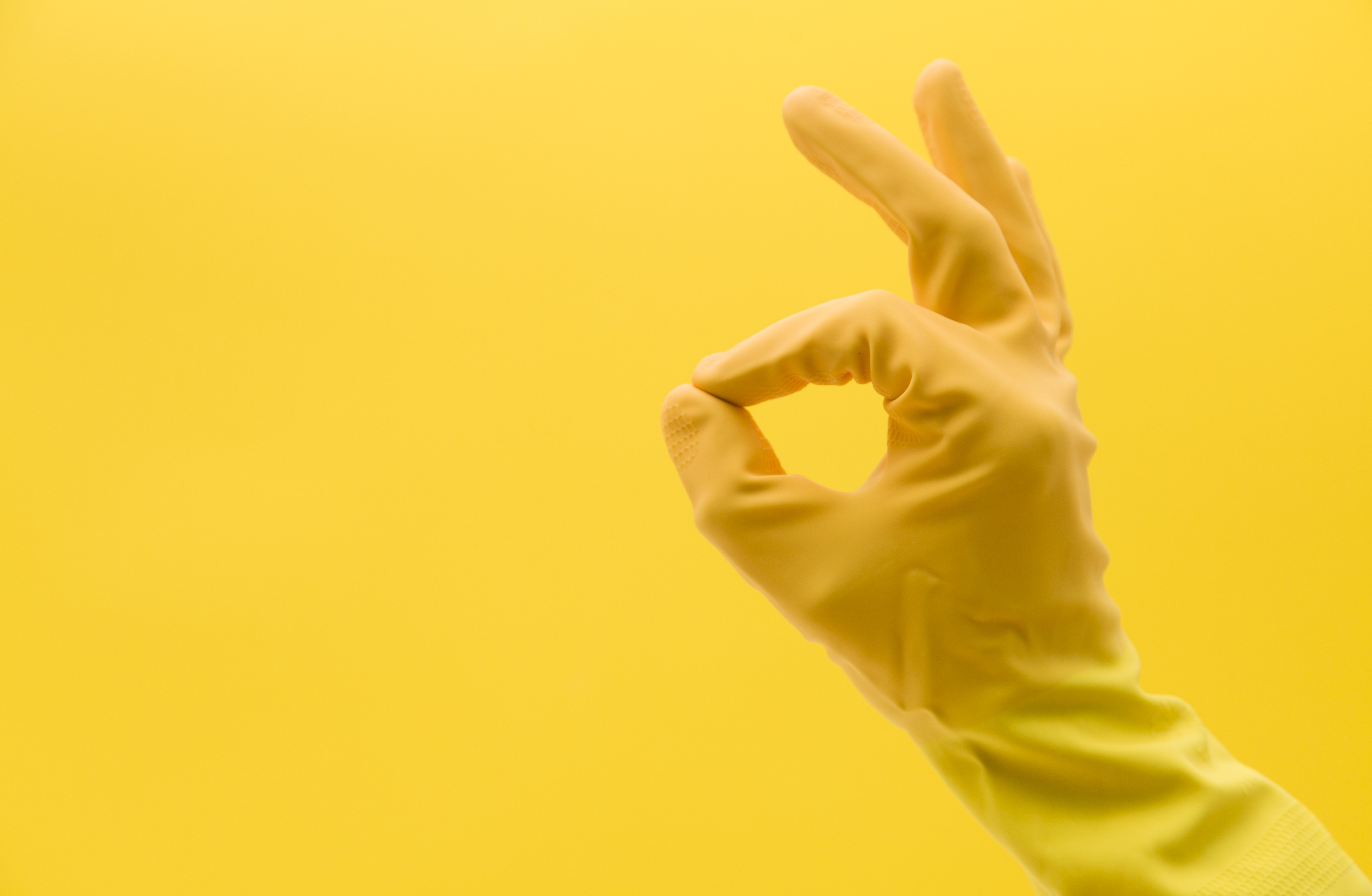 A yellow-gloved hand makes the okay symbol.