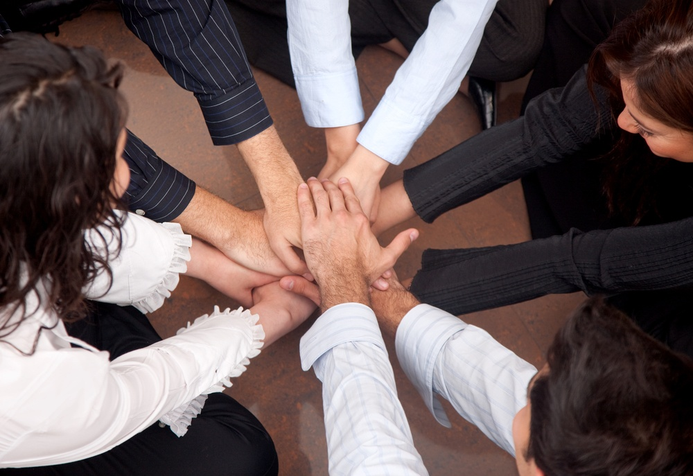 business people teamwork in an office with hands together.jpeg