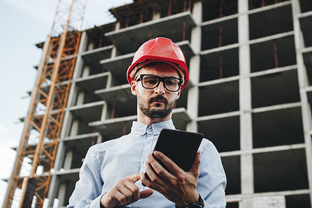 Integrator at construction site reviewing cell signal specifications on tablets