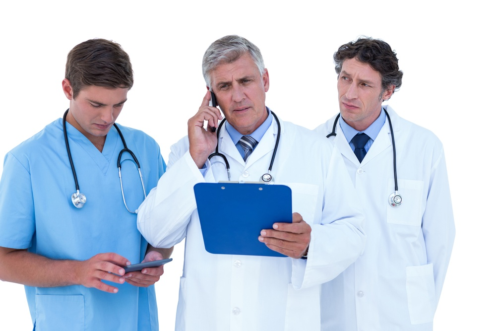 A doctor on the phone holding a clipboard and using his cell phone