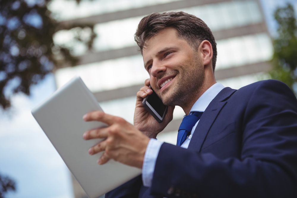 Businessman holding digital tablet and talking on mobile phone