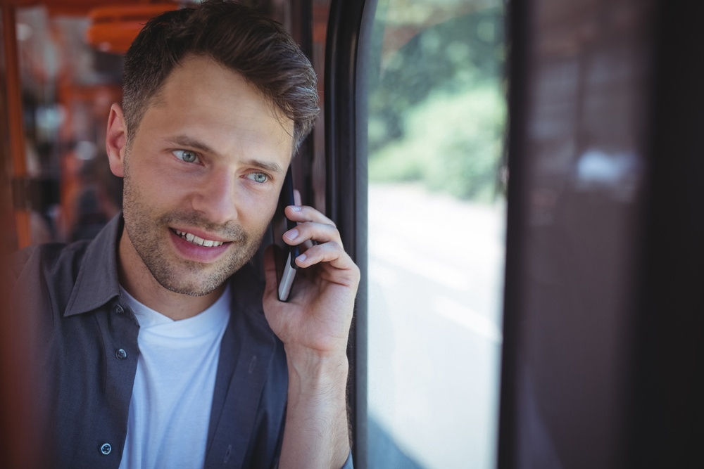 Handsome man talking on mobile phone in bus