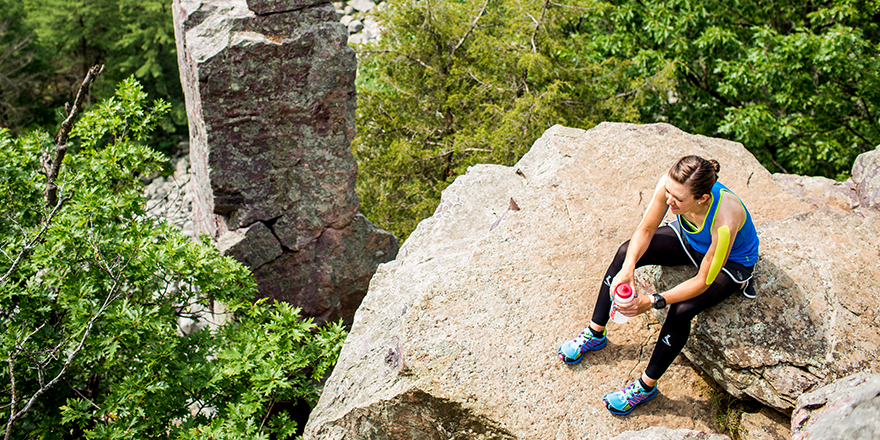 woman taking a break from hiking at the top of a cliff