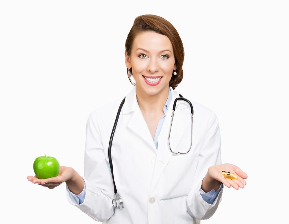 Closeup portrait smiling, female health care professional, family doctor, endocrinologist, nutritionist holding green apple, pills, vitamins. Diet modification, diabetes management, drugs alternative
