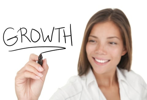 "A woman focused her pharmacy business writes the word ""growth"" with a black marker"